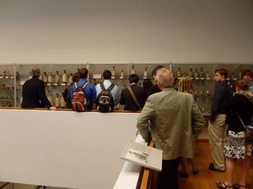 Students examine white ground lekythoi in the restricted upper gallery