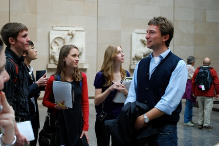 Dr. Scott lectures about the Parthenon sculpture as Joe, Kathryn, and KT listen intently.