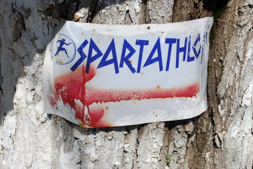 "A directional sign for the famed ""Spartathon"" (an annual 36-hour ultramarathon from Athens to Sparta) in the plateia at Tegea."