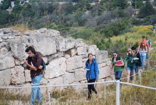 "Jason, Kathryn, et al file past the unexcavated Middle Helladic ""mansion"" at Kolonna."