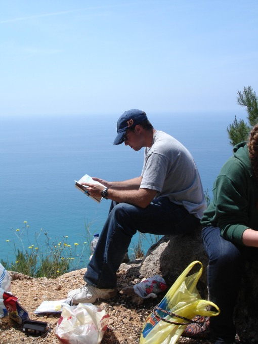 Chris reads the Iliad in front of the Adriatic.