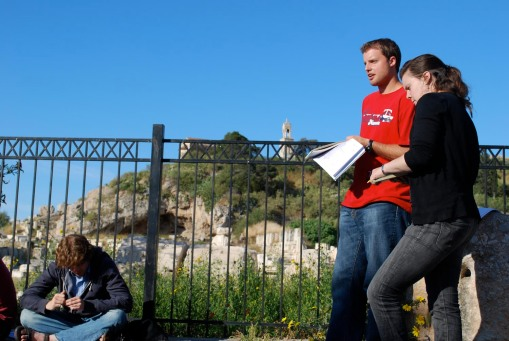 Chris asks a question while Ally and Alex A take notes in front of the Eleusinian acropolis.