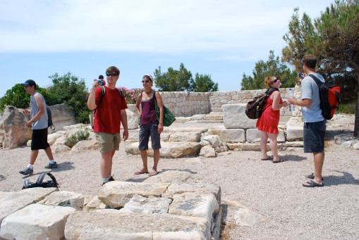 Ben, Charlie and Prof. Faro consider the remains of the temple of Athena while Chris momentarily relieves Kait's of her self-photography duties.
