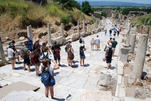 The group pauses atop the main road at Ephesus to peer down to the library of Celsus.