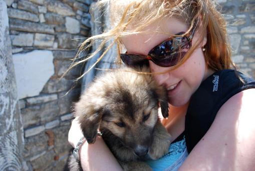 Kait nuzzles a fuzzy puppy.