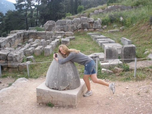 KT reaches back to her Minoanophile roots, hugging the pseudo-baetylic omphalos at Delphi.