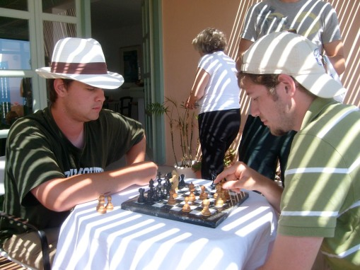 Charile and Alex A. indulge in a game of Chess back at the hotel.